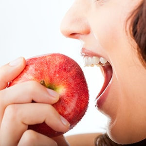 Someone biting into an apple after getting dental implants